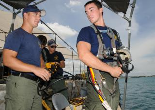 Sailors from the submarine tender USS Frank Cable, assist with air hose check before diving by Flickr user Official U.S. Navy Imagery