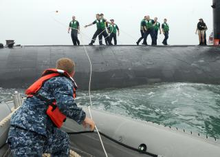 Sailor assigned to USS Frank Cable (AS 40), throws a heaving line to Sailors aboard USS Hampton by Flickr user Official U.S. Navy Imagery